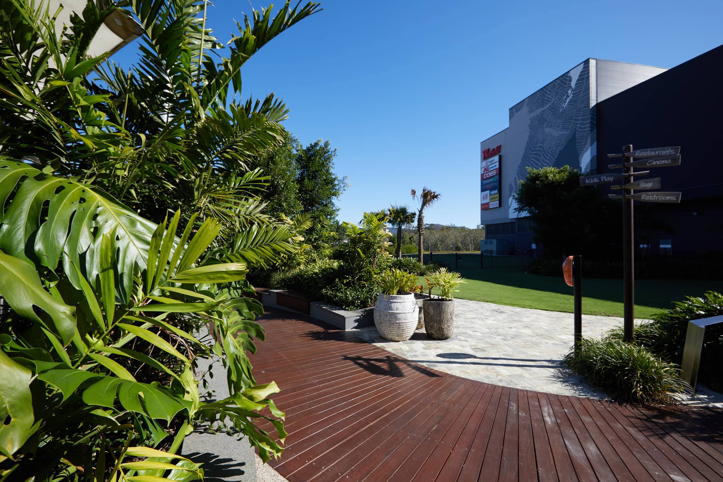 A professional photograph of a boardwalk in the outdoor area of retail shopping centre. The boardwalk has garden beds and potted plants all along it, with a Westfield sign in the background.