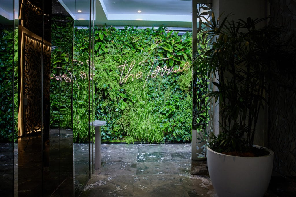 The striking entrance to The Terrace rooftop bar at Emporium South Bank Brisbane, featuring a green wall with their branding in neon lights.