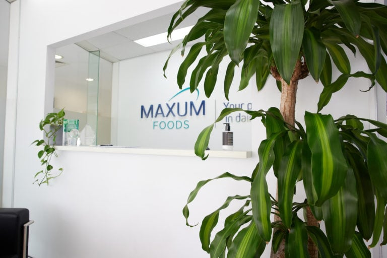The reception of Maxum Foods in Milton with a potted floor Happy plant and trailing pothos.